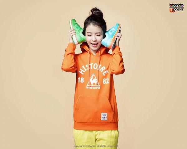 Tags: K-Pop, IU, Eyes Closed, Shoes, Hair Buns, Orange Shirt, Hoodie, Single Bun, Hair Up, Le Coq Sportif