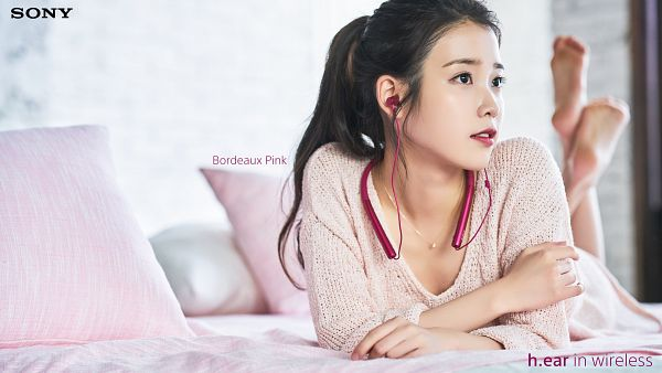 Tags: K-Pop, IU, Pillow, Pink Shirt, Laying On Stomach, Barefoot, Red Lips, Hair Up, Text: Brand Name, Laying Down, Bed, English Text