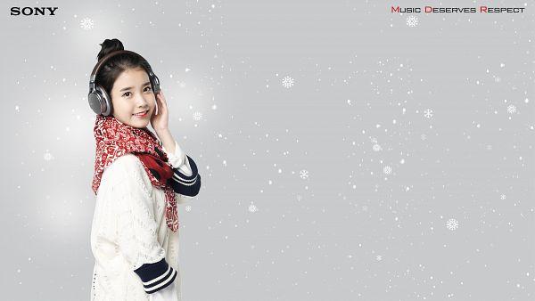 Tags: K-Pop, IU, White Outerwear, Hood, Hand On Head, Gray Background, Hair Up, Sweater, Single Bun, Snow, White Jacket, Headphones