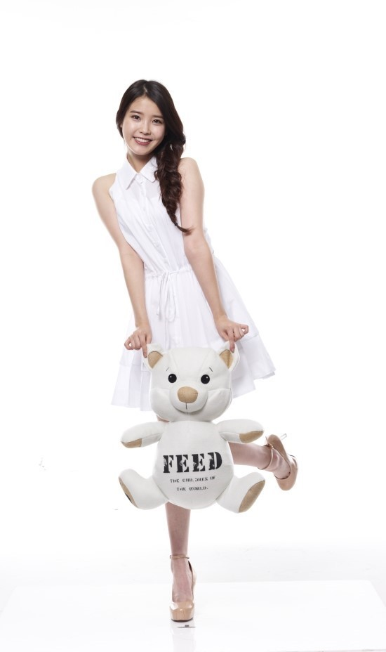 Tags: K-Pop, IU, White Dress, Sleeveless Dress, White Outfit, Stuffed Animal, Sleeveless, Standing On One Leg, Light Background, Brown Footwear, High Heels, Braids
