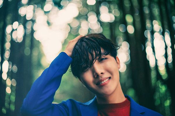 Tags: K-Pop, BTS, J-Hope, Plant, Tree, Outdoors, Grin, Hand On Head, Red Shirt, Blue Outerwear, Blue Jacket, Black Eyes