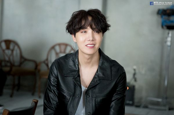 Tags: K-Pop, BTS, J-Hope, Grin, Indoors, Wavy Hair, Leather Jacket, Text: URL, Black Jacket, Chair, Black Outerwear, English Text