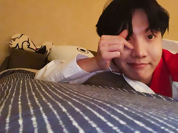Tags: K-Pop, BTS, J-Hope, Wink, Indoors, Bed, Laying Down, Heart Gesture, On Bed, Pillow, Twitter, Selca