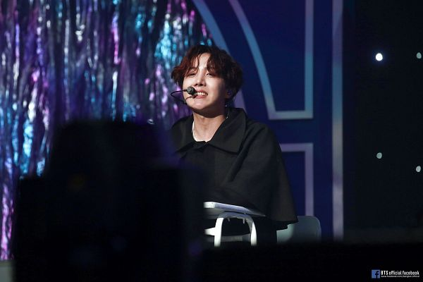 Tags: K-Pop, Bangtan Boys, J-Hope, English Text, Curtain, Collar (Clothes), Grin, Text: Artist Name, Sitting, Black Outerwear, Text: URL, Microphone