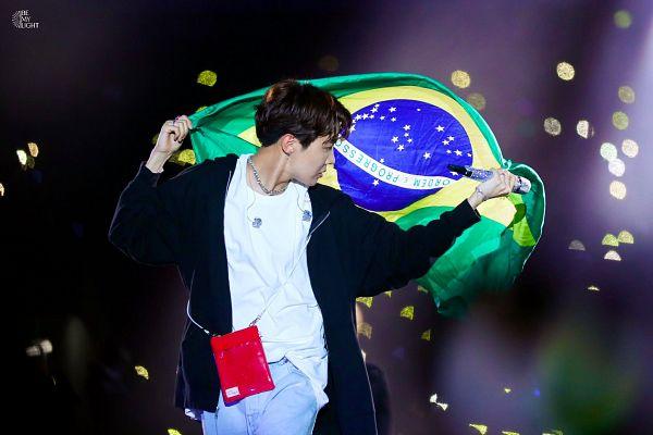 Tags: K-Pop, BTS, J-Hope, Necklace, Earbuds, Jeans, Looking Back, Flag, Bag, Black Jacket, Blue Pants, Country Flag