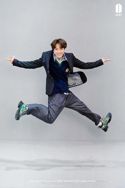 Tags: K-Pop, BTS, J-Hope, Blue Shirt, Gray Pants, Grin, Gray Background, Jumping