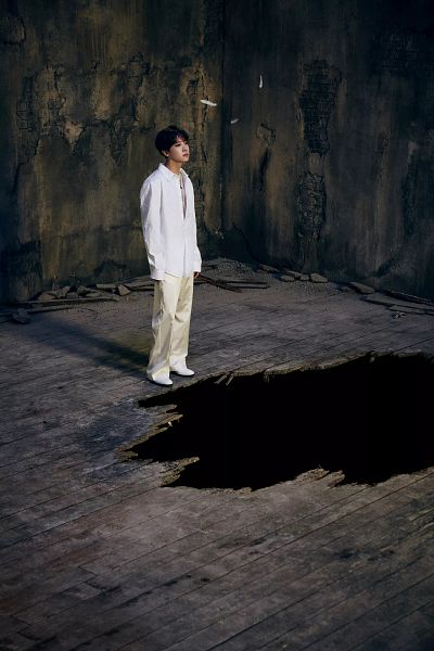 Tags: K-Pop, BTS, J-Hope, Necklace, Feather, White Footwear, Hole, White Outfit, White Pants, Shoes, Indoors, Dark Background