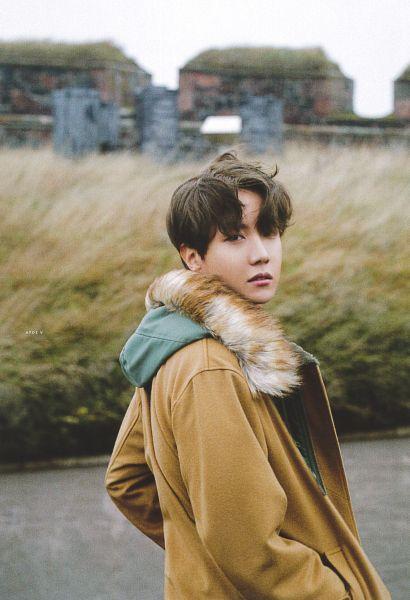 Tags: K-Pop, BTS, J-Hope, Wind, Brown Outerwear, Flowing Hair, Coat, Fur, Fur Trim, Black Eyes, Outdoors, Grass