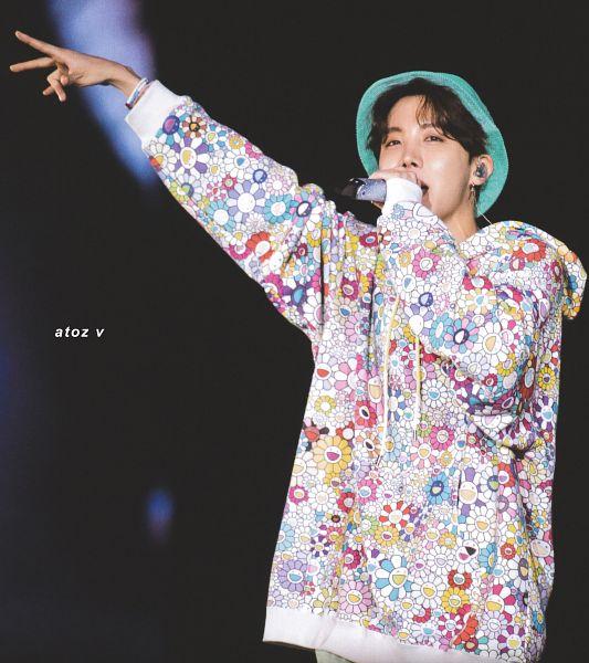 Tags: K-Pop, BTS, J-Hope, Dark Background, Holding Object, Floral Print, Hat, Earbuds, Bracelet, Hood, Hoodie, One Arm Up