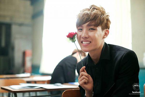 Tags: K-Pop, Bangtan Boys, J-Hope, Grin, Black Shirt, Sitting, Short Hair, Teeth, Flower, Rose (flower), Holding Object, Table