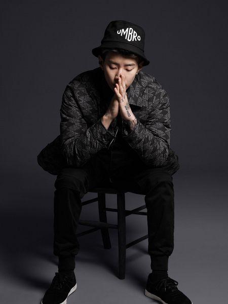 Tags: K-Pop, Jaebom, Sneakers, Covering Mouth, Shoes, Dark Background, Black Pants, Black Footwear, Hat, Looking Down, Full Body, Chair