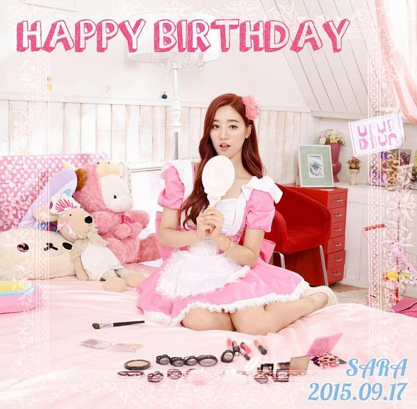 Tags: K-Pop, VIVIDIVA, Jeon Sara, Text: Calendar Date, Pink Outfit, On Bed, Bed, Text: Happy Birthday, Stuffed Animal, Text: Artist Name, Red Hair, Toy
