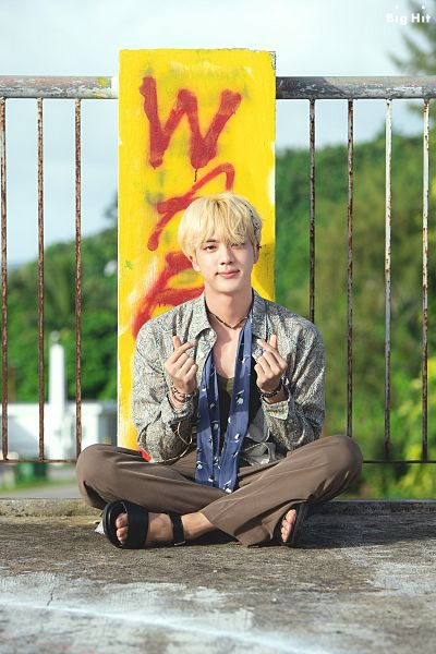Tags: K-Pop, BTS, Jin, Heart Gesture, Black Footwear, Text: Company Name, Necklace, Crossed Legs, Mound, Bracelet, Sandals, English Text