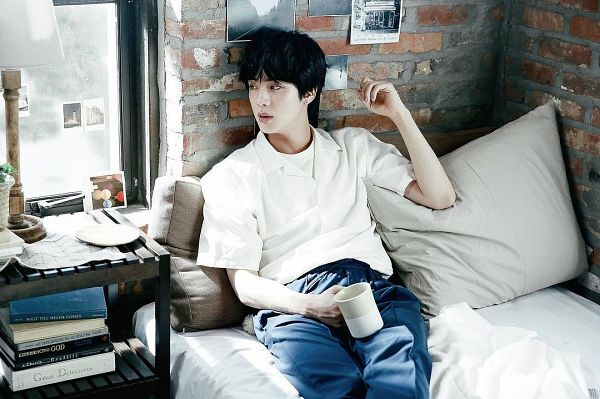 Tags: K-Pop, BTS, Jin, Table, Cup, Window, Indoors, Blue Pants, Pillow, Bed, Looking Away, On Bed