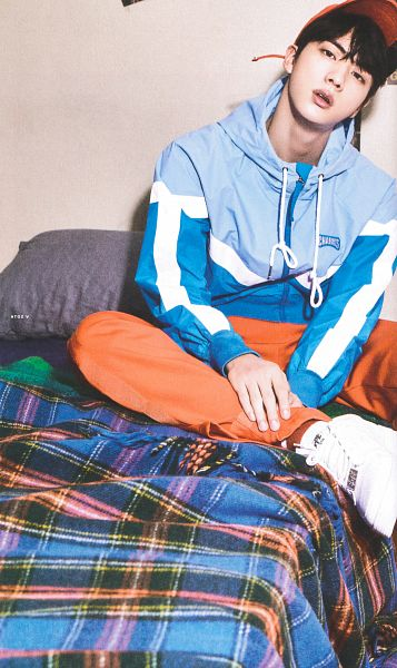 Tags: K-Pop, BTS, Jin, Sneakers, Hat, Hand On Leg, Blue Outerwear, Hood, White Footwear, Bed, Orange Headwear, Pillow