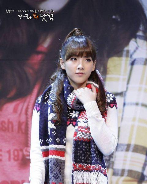 Tags: K-Pop, KARA, Jiyoung Kang, Wavy Hair, Korean Text, Scarf, White Outerwear, Black Neckwear, Looking Away, Sweater