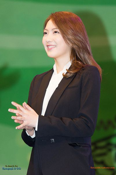 Tags: K-Pop, KARA, Jiyoung Kang, Clapping, Green Background, Looking Up, Black Outerwear, Black Jacket, Toto, Android/iPhone Wallpaper