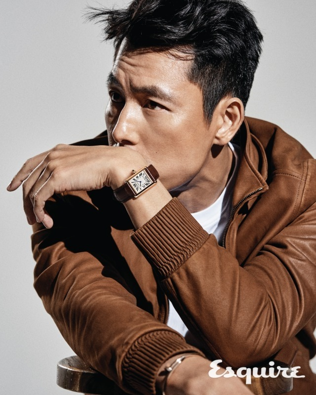 Tags: K-Drama, Jung Woosung, Covering Mouth, Watch, Text: Magazine Name, Brown Outerwear, Looking Ahead, Gray Background, Esquire Magazine