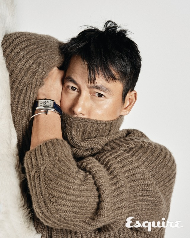 Tags: K-Drama, Jung Woosung, Brown Shirt, Laying Down, Turtleneck, Laying On Side, Covering Mouth, Sweater, Collar (Clothes), Text: Magazine Name, Watch, Esquire Magazine