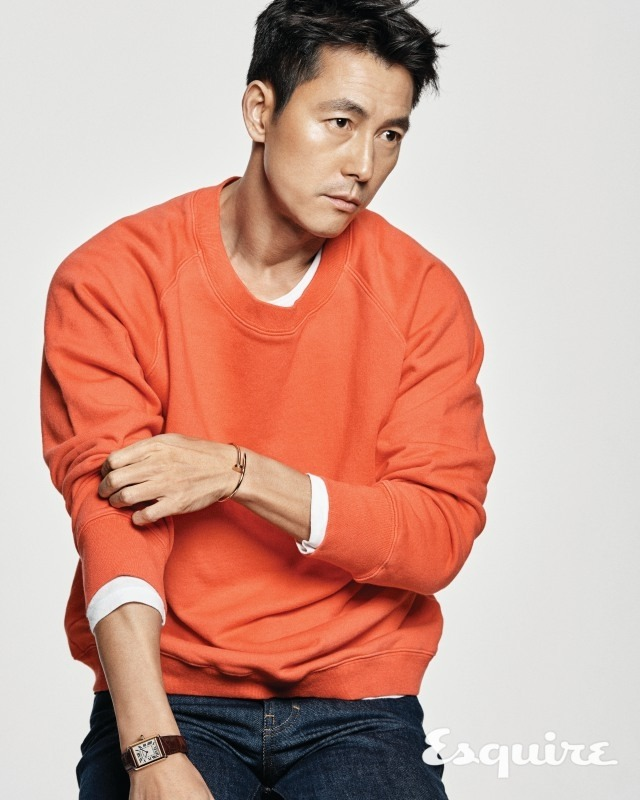 Tags: K-Drama, Jung Woosung, Blue Pants, Gray Background, Text: Magazine Name, Watch, Looking Ahead, Jeans, Orange Shirt, Bracelet, Esquire Magazine