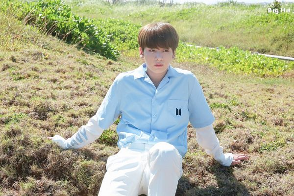 Tags: K-Pop, BTS, Jungkook, Grass, Blue Shirt, Sitting On Ground, Looking Away, White Pants, Text: Company Name, BTS 2018 Season's Greetings