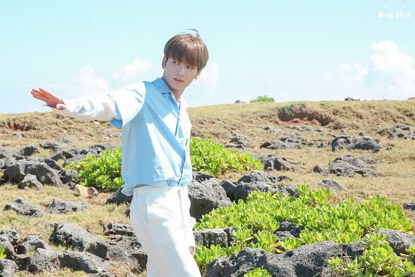Tags: K-Pop, BTS, Jungkook, Arms Out, Plant, Blue Shirt, Text: Company Name, Rocks, White Pants, Day, Clouds, Sky