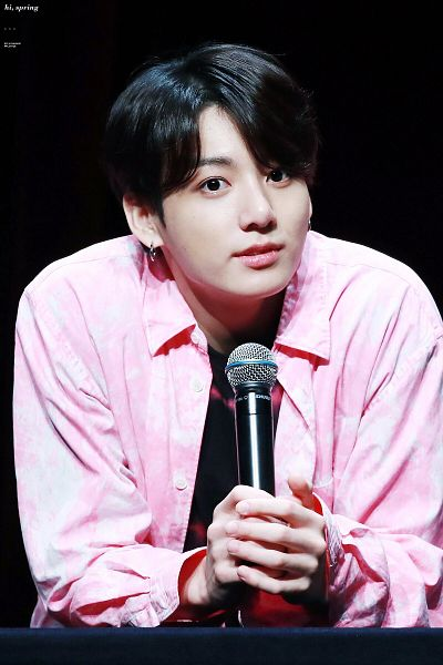 Tags: K-Pop, BTS, Jungkook, Pink Outerwear, Collar (Clothes), Holding Object, Black Background, Close Up, Pink Jacket, Black Eyes, English Text, Dark Background