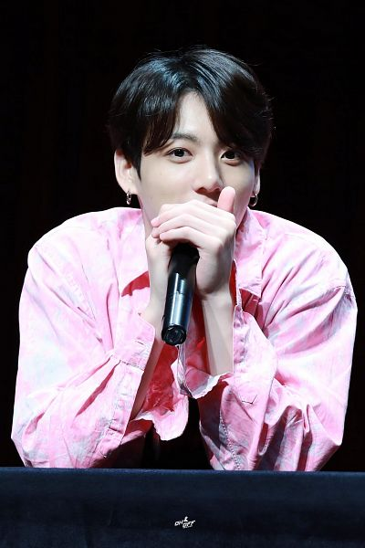 Tags: K-Pop, Bangtan Boys, Jungkook, Holding Object, Black Background, Close Up, Pink Jacket, Black Eyes, English Text, Microphone, Dark Background, Pink Outerwear