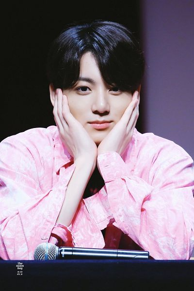 Tags: K-Pop, Bangtan Boys, Jungkook, Close Up, Pink Outerwear, Collar (Clothes), English Text, Black Eyes, Hand On Cheek, Pink Jacket, Microphone, Hand On Head