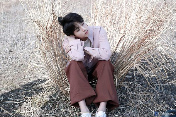 Tags: K-Pop, BTS, Jungkook, Looking Away, Brown Pants, Pink Shirt, Grass, Shoes, Plant, Sitting On Ground, Shadow, Outdoors