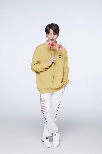 Tags: K-Pop, BTS, Jungkook, Flower, White Footwear, White Pants, Sneakers, Yellow Shirt, Shoes, Crossed Legs (Standing), Pink Flower, Puma