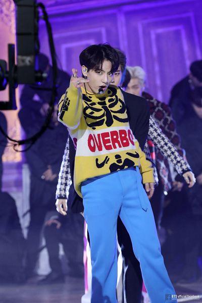 Tags: K-Pop, BTS, Dionysus, Jungkook, Blue Pants, English Text, Yellow Shirt, Text: URL, Ring, Singing, Black Eyes, Stage