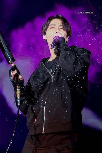Tags: K-Pop, BTS, Jungkook, Earbuds, Purple Background, Weapons, Gun, Black Pants, Holding Weapon, Singing, Black Eyes, Live Performance
