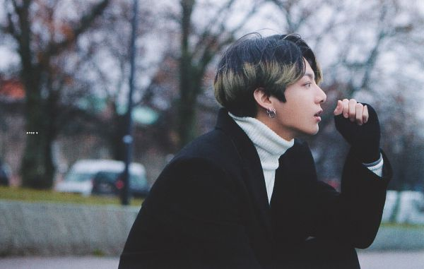 Tags: K-Pop, BTS, Jungkook, Outdoors, Multi-colored Hair, Black Outerwear, Collar (Clothes), Side View, Turtleneck, Tree, Coat, Plant