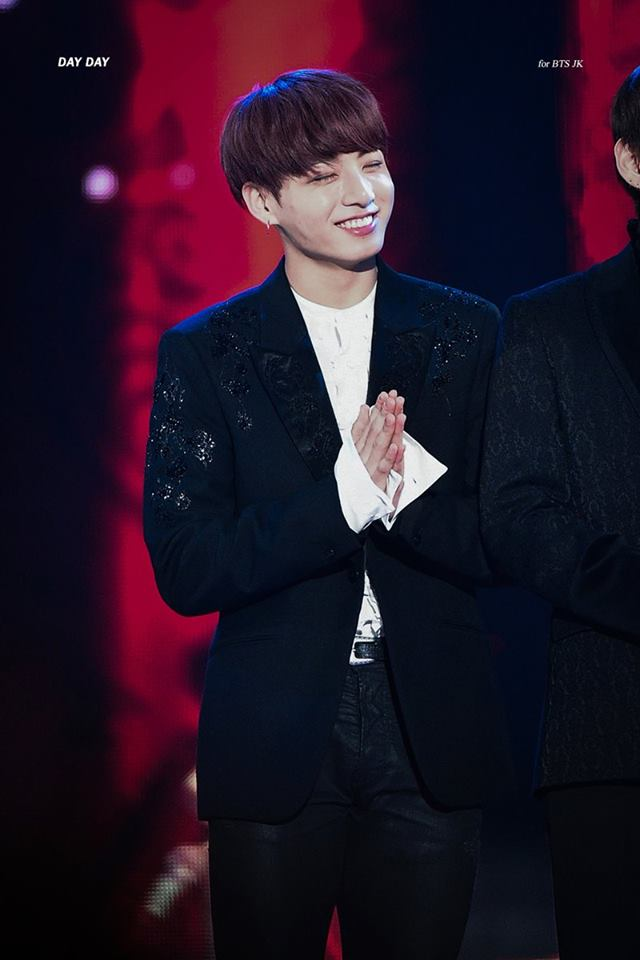 Tags: K-Pop, BTS, Jungkook, Ring, Eyes Closed, Stage, Black Outerwear, Black Pants, Clasped Hands, Black Jacket