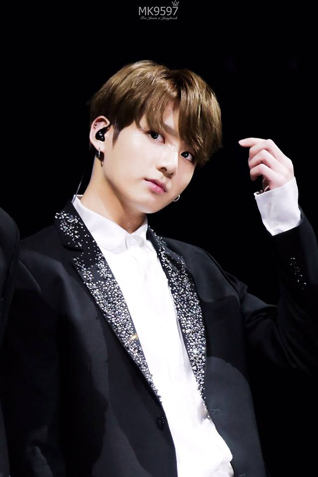 Tags: K-Pop, BTS, Jungkook, Black Eyes, Serious, Earbuds, One Arm Up, Dark Background, Black Jacket, Stage, Black Background, Black Outerwear