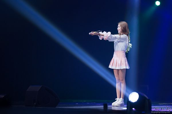 Tags: K-Pop, Berry Good, Kang Sehyung, Side View, Wavy Hair, Microphone, Spotlight, Skirt, Stage, Full Body, Pink Skirt