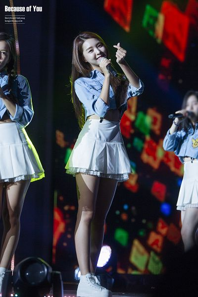 Tags: K-Pop, Berry Good, Kang Sehyung, Blue Shirt, Rolled Up Sleeves, Skirt, Head Tilt, Spotlight, White Skirt, Full Body, Stage, Heart Gesture