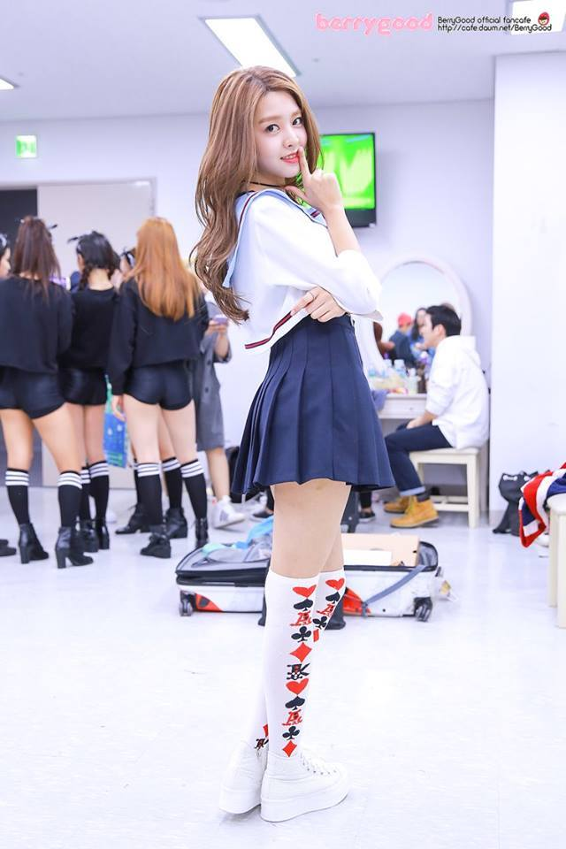 Tags: K-Pop, Berry Good, Kang Sehyung, Wavy Hair, Self Hug, Skirt, Mole, Finger To Lips, Shush, Blue Skirt, Standing, Pleated Skirt