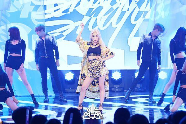 Tags: K-Pop, Kim Chung-ha, Hand On Hip, Black Footwear, High Heels, Blue Background, Bracelet, Yellow Outerwear, Skirt, Yellow Skirt, Midriff, Bare Legs