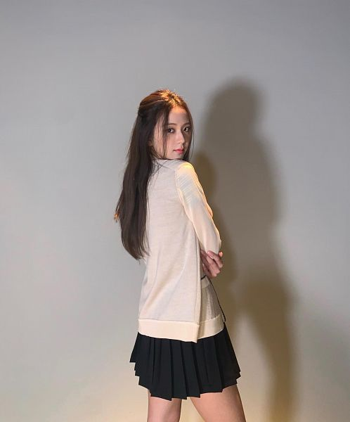 Tags: K-Pop, Black Pink, Kim Jisoo, Gray Background, Skirt, Crossed Arms, Pleated Skirt, Looking Back, Bare Legs, Black Skirt