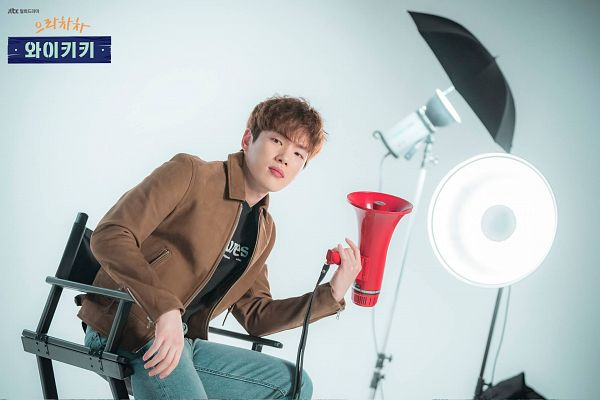 Tags: K-Drama, Kim Jung-hyun, Chair, Blue Pants, Sitting, Korean Text, Sitting On Chair, Brown Outerwear, Black Shirt, Jacket, Megaphone, Bent Knees