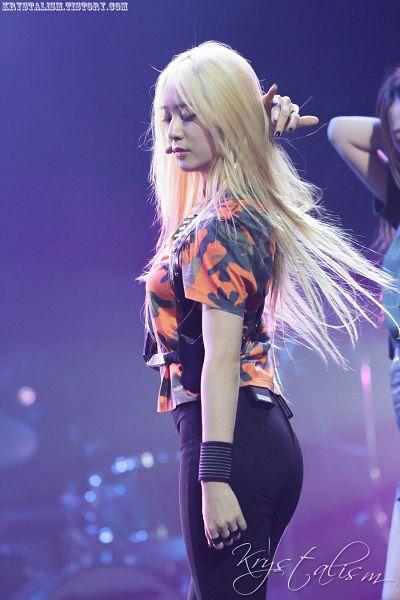 Tags: K-Pop, f(x), Krystal Jung, Eyes Closed, Wristband, Black Pants, Hand In Hair, Orange Shirt, Side View, Camouflage Print, Blue Background, Krystalism