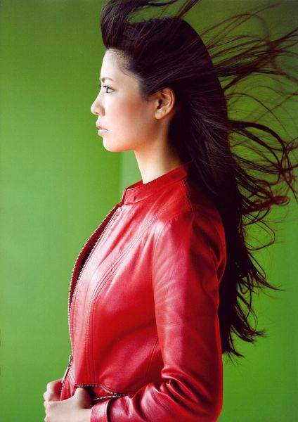Tags: J-Pop, AKB48, Kuramochi Asuka, Hand In Pocket, Messy Hair, Side View, Red Jacket, Leather Jacket, Green Background, Red Outerwear, Android/iPhone Wallpaper