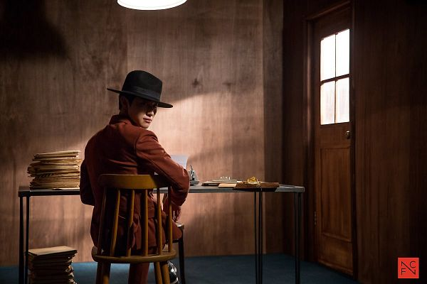 Tags: K-Drama, Kwak Dong-yeon, Tie, Sitting On Chair, Chair, Door, Jacket, Orange Outerwear, Looking Back, Short Hair, Bent Knees, Hat
