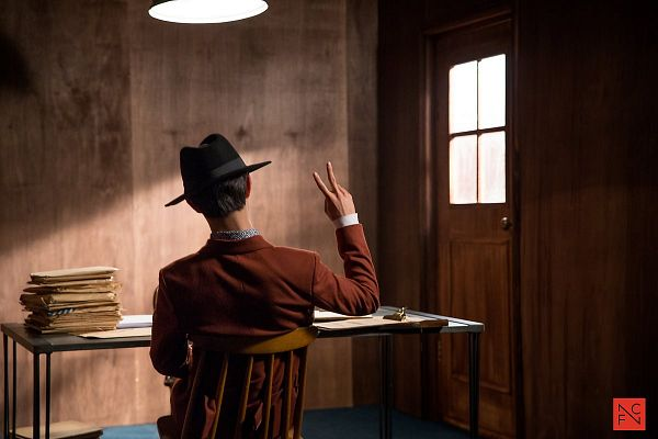 Tags: K-Drama, Kwak Dong-yeon, V Gesture, Table, Bent Knees, Short Hair, Lamp, Sitting, Hat, Sitting On Chair, Tie, Door