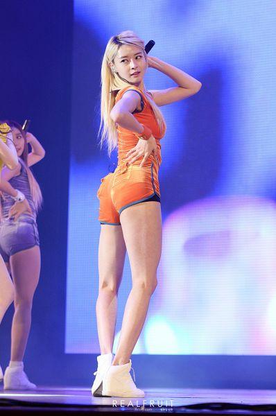 Tags: K-Pop, Hello Venus, Wiggle Wiggle, Kwon Nara, Looking Back, Suggestive, Orange Shirt, English Text, Orange Shorts, Blue Background, Shoes, White Footwear