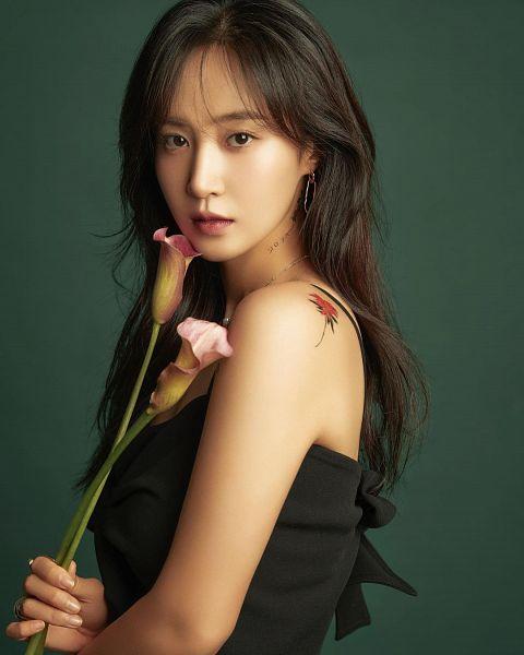 Tags: K-Pop, Girls' Generation, Kwon Yuri, Black Outfit, Bare Shoulders, Green Background, Black Dress, Bare Back, Tattoo, Sleeveless, Sleeveless Dress, Pink Flower