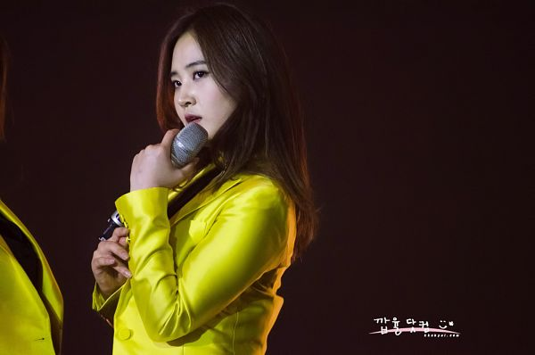 Tags: K-Pop, Girls' Generation, Kwon Yuri, Yellow Outerwear, Brown Background, Looking Away, Kkabyul