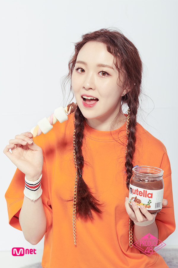 Tags: Television Show, K-Pop, Lee Chaejeong, Candy, Braids, Twin Braids, Text: Series Name, Orange Shirt, Marshmallow, Close Up, Short Sleeves, Sweets